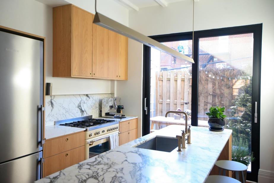 Malgré une pièce étroite, la cuisine fabriquée par Éco-Ébénisterie dispose d'espaces de préparation, de rangement et de réception appréciables. Suspension de Lambert&Fils.