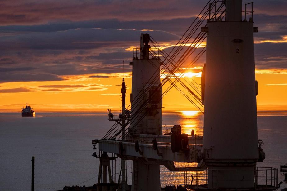 Le soleil se lève sur le Saint-Laurent, entre les grues du navire.