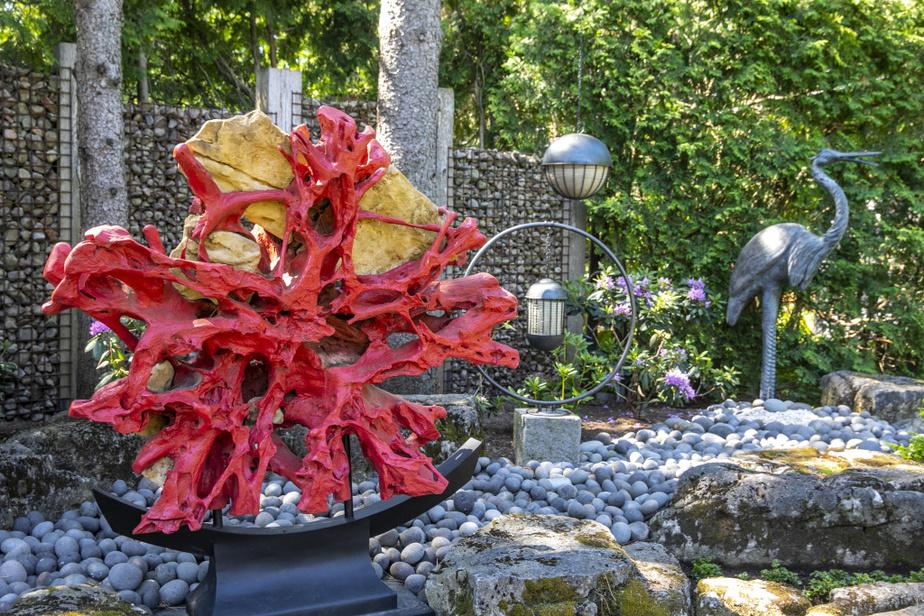 Dans le jardin zen d'inspiration japonaise, cette sculpture représente le soleil levant. Il s'agit à la base d'une racine d'arbre, découverte à Bali, qui a été arrondie et peinte, avant d'être placée sur un piédestal de style japonais. Les roches à l'arrière proviennent aussi de Bali.