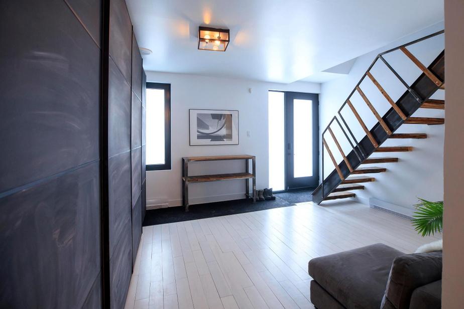 Dès le hall d'entrée, l'escalier en bois récupéré et en acier donne le ton à la maison. Le rangement, à gauche, est un PAX d'Ikea sur lequel une peinture ardoise a été appliquée.