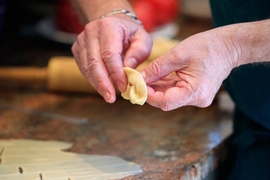 Avec ses mains, on prend un rectangle de pâte et on passe une partie de la pâte à travers l'incision pour en faire un nœud.