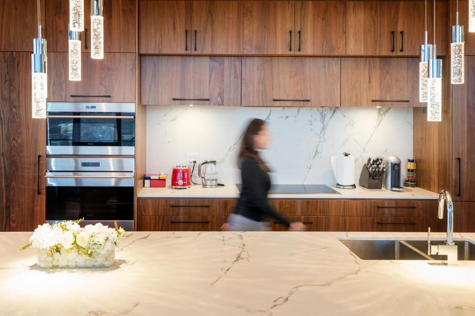 Dans la cuisine, les armoires en noyer réchauffent l'atmosphère. De la pierre sintérisée de marqueDektona été privilégiée pour former les plans de travail et le dosseret.