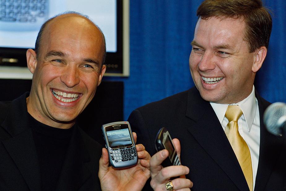 Le PDG de Research In Motion, Jim Balsillie (à gauche), lors de l'annonce en avril 2006 de l'ouverture d'un nouveau centre d'opérations, affiche fièrement son BlackBerry en compagnie du premier ministre de la Nouvelle-Écosse, Rodney MacDonald.
