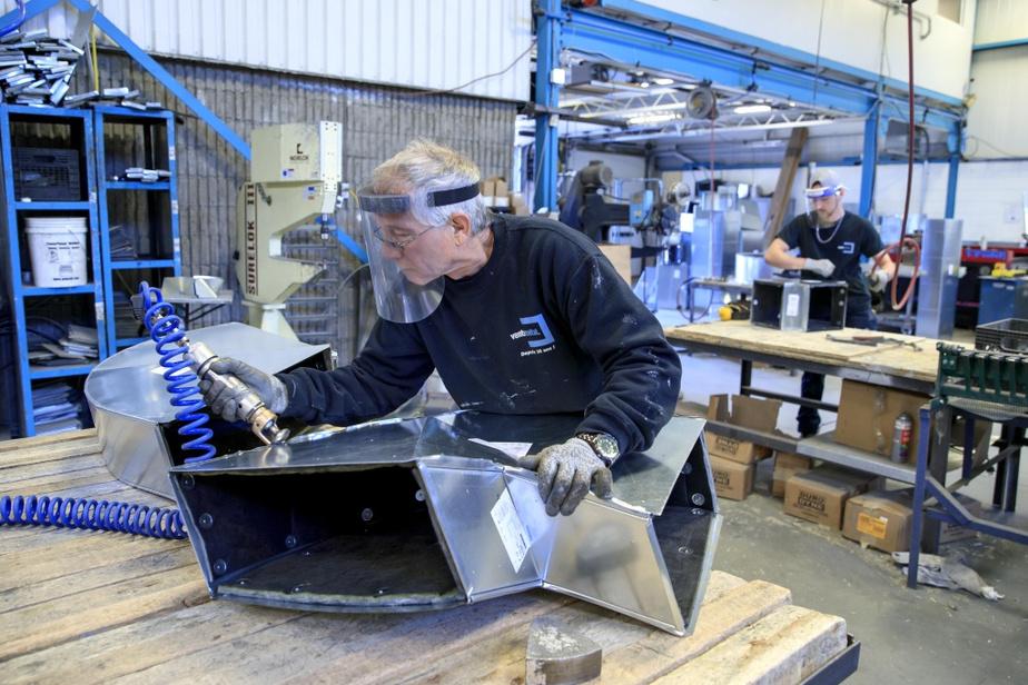 Chez Ventimétal, à Laval, les employés comme les ferblantiers Daniel Lalande (premier plan) et Paul-Guillaume Tessier-Martineau sont invités à porter la visière, à rester le plus possible à leur poste de travail et à ne pas partager leurs outils.