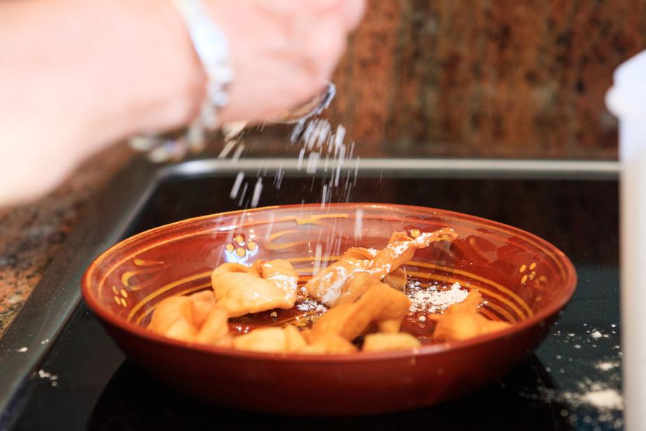 À chaque fournée de sept bugnes, on saupoudre un peu de sucre en poudre (sucre glace) sur les bugnes que l'on empile ensuite, de préférence dans un saladier.