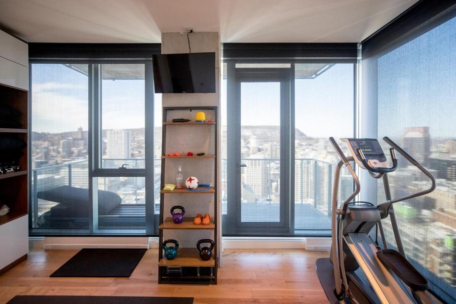 Une des pièces, au deuxième niveau, a été transformée en salle d'exercice. Même avec les stores baissés, aux fins de la photo, il est possible d'apprécierla vue.