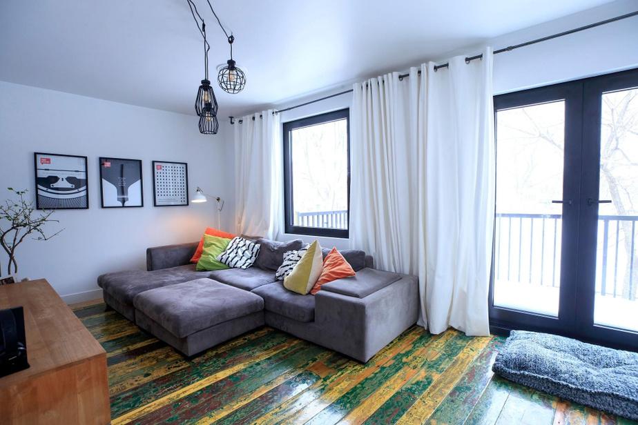 Le plancher de la salle familiale du deuxième étage détonne avec celui des autres pièces de la maison. Les propriétaires ont tenu à conserver ces planches colorées qui proviennent d'une ancienne grange.