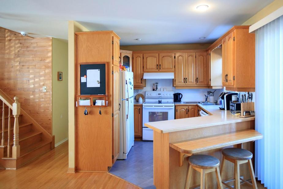 La cuisine est l'un des irritants majeurs de la maison, selon Pascal et Sophie: armoires en chêne, angles nombreux, frigo vieux de 25ans (le seul qui entre dans l'espace) et double évier en coin, séparé. Faute de place, une partie du garde-manger a été relocalisée dans une armoire de la salle à manger.