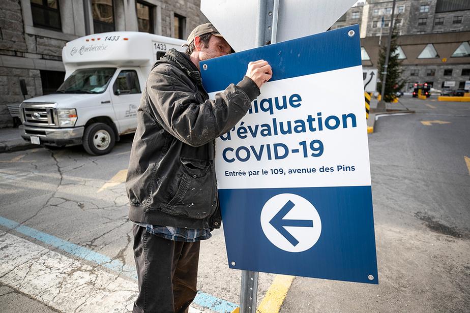 À Montréal, des travailleurs installent des affiches pour orienter les patients vers l'entrée de la clinique dedépistage située dans les anciennes urgences de l'Hôtel-Dieu.