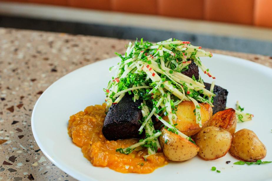 Un plat de boudin accompagné de pommes de terre grelots, ketchup de pommes et petite salade de pommes en julienne et ciboulette.