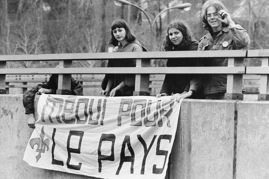 Des partisans du Oui accrochent une banderole sur un viaduc.