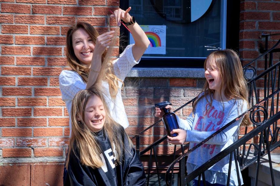 La coiffeuse Brigitte Marsh, qui donne des trucs pour couper les cheveux à la maison, entourée de ses filles Maxim, 9ans, et Simone, 6ans.