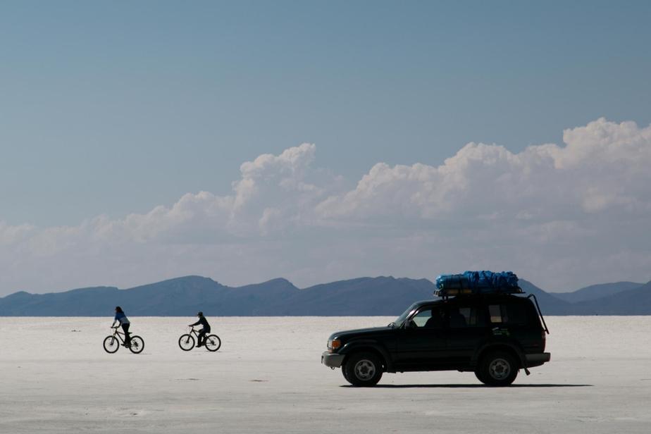 Deux cyclistes se promènent sur le sel pendant que des touristes passent tout près.