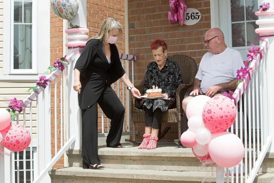 José Larose apporte un gâteau d'anniversaire à sa mère Thérèse Morin, qui est flanquée de son conjoint Aimé Paré.