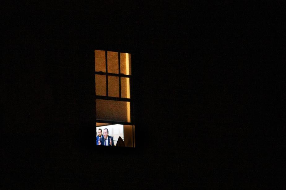 De l'autre côté de la fenêtre, un Montréalais regarde le point de presse du premier ministre FrançoisLegault.