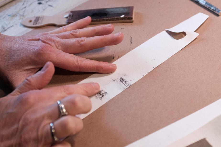 «Faire des arbres, c'est ce que je préfère», dit l'artiste. Elle évoque l'écorce du bouleau en appliquant de la poussière de fusain au doigt, sur un carton blanc découpé.