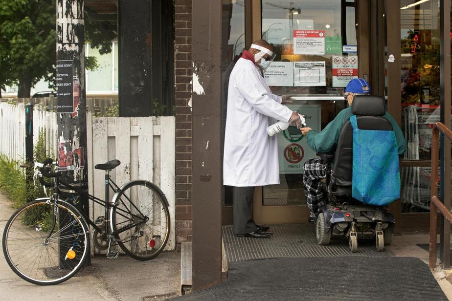 Un employé désinfecte les mains d'un client à l'entrée d'une épicerie de Montréal.