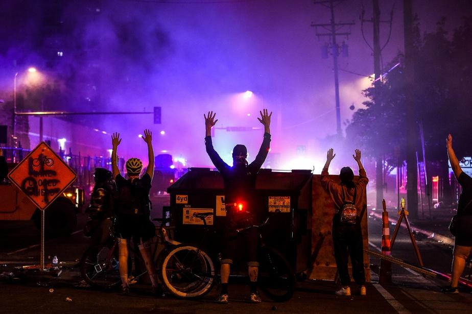 Des manifestants lèvent les mains alors qu'ils regardent en direction des forces policières, à Minneapolis.