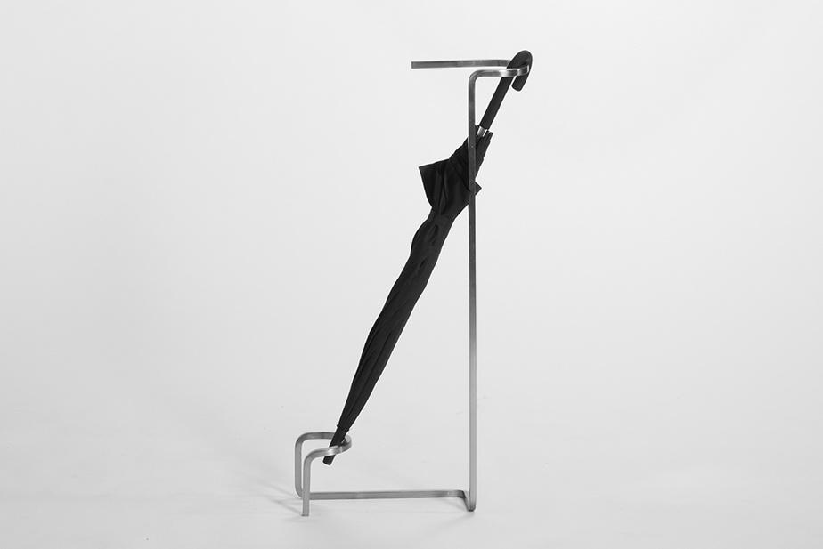 En acier moulé dans des lignes épurées, le porte-parapluie Zone grise, signé Charlotte Gori, (150$).