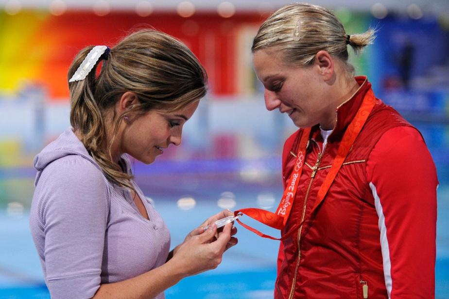 AnniePelletier regarde la médaille de son amie, la plongeuse ÉmilieHeymans, après les Jeux olympiques de Pékin, en 2008.