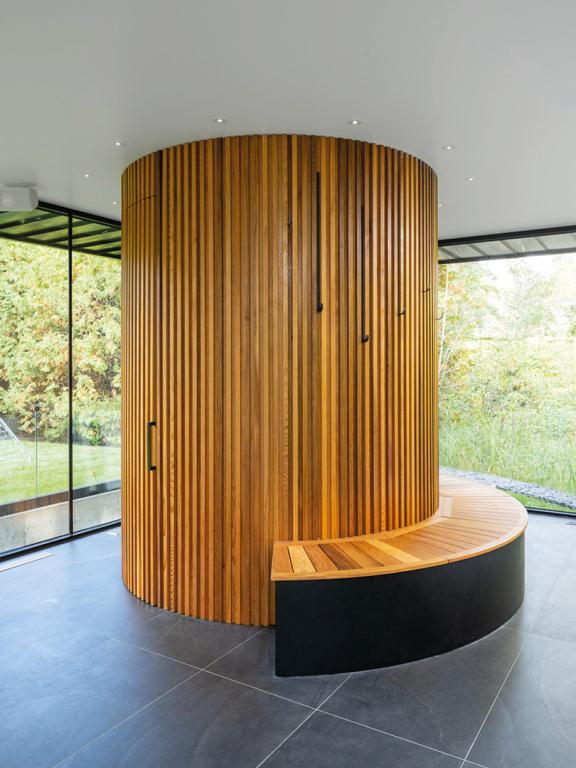 Un banc épouse la forme cylindrique faite de lattes de cèdre rouge, à l'intérieur de laquelle se trouve la salle de bains.