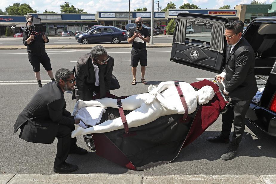 L'artiste visuel montréalais Stanley Février, à gauche, et ses collaborateurs sortent d'un corbillard une sculpture représentant GeorgeFloyd, dont la mort sous le genou d'un policier a suscité une vague de protestations contre le racisme et la brutalité policière dans le monde.