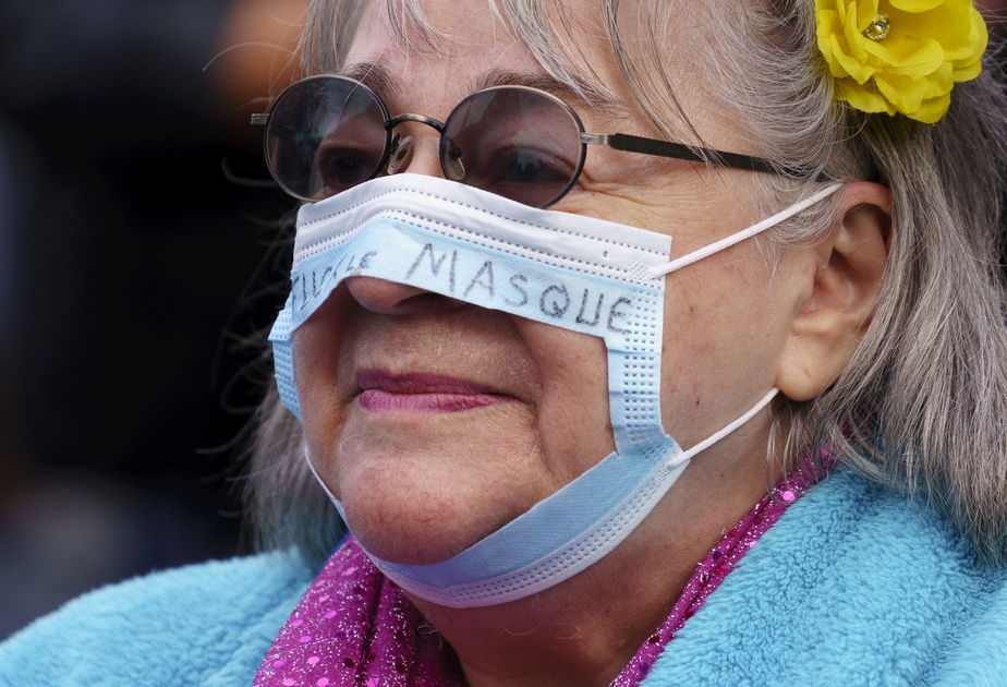 Une manifestante lors d'un rassemblement antimasque. «Fuck le masque», peut-on lire sur ce couvre-visage mutilé pour la cause.