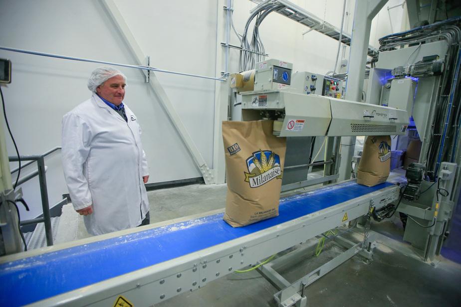 RobertBeauchemin, propriétaire de la Meunerie Milanaise, devant la chaîne d'emballage