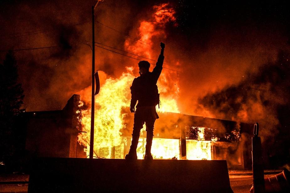 Un manifestant se tient devant un immeuble incendié lors d'une manifestation à Minneapolis, vendredi soir.