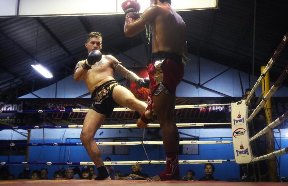 Un boxeur canadien (à gauche) affronte un champion local. À grands coups de pieds ravageurs, il est parvenu à remporter ce combat.
